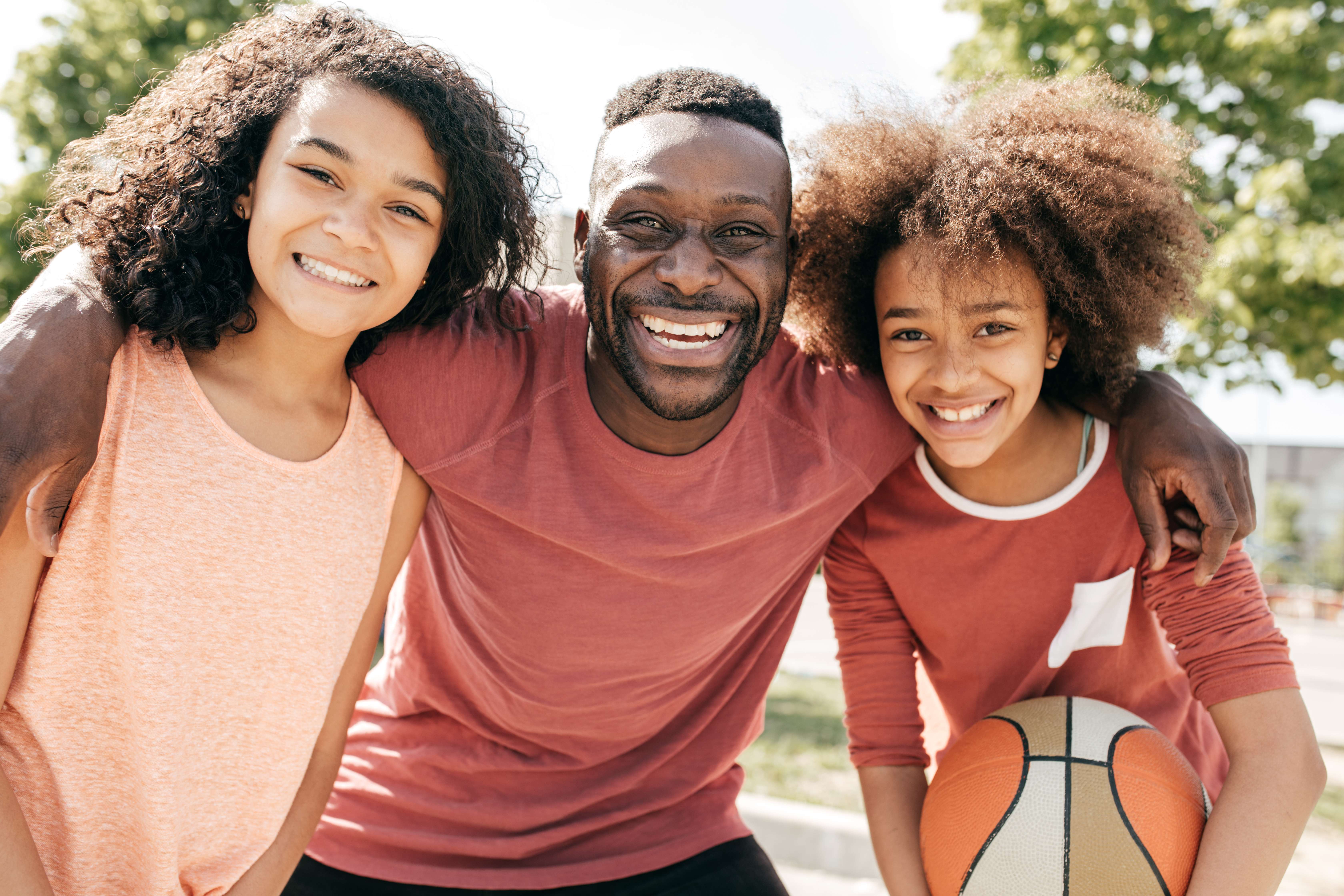 Dad and daughters posing with basketball ball