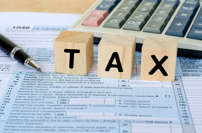 Tax Word on Wooden Block With Calculator and Tax Form