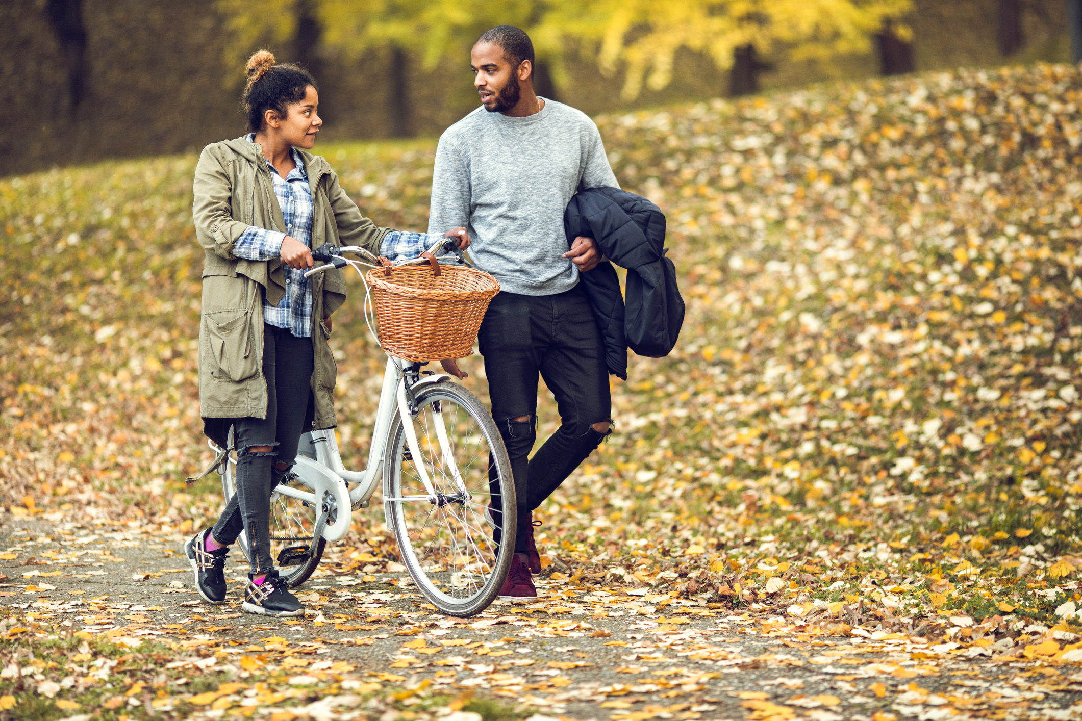 Full length of young African American couple walking in the park and communicating.