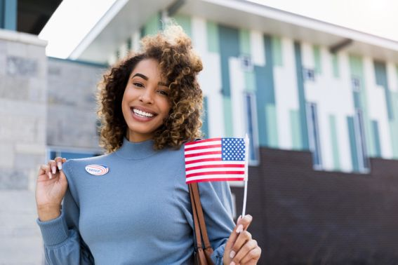 """Woman smiles for camera and shows off """"I voted"""" sticker"""