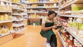 supermarket employee ordering groceries, using bar code reader