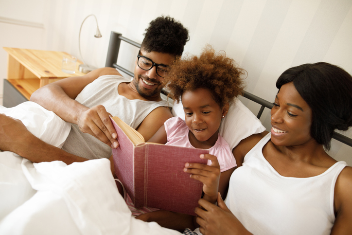 Happy family reading an interesting book in bed