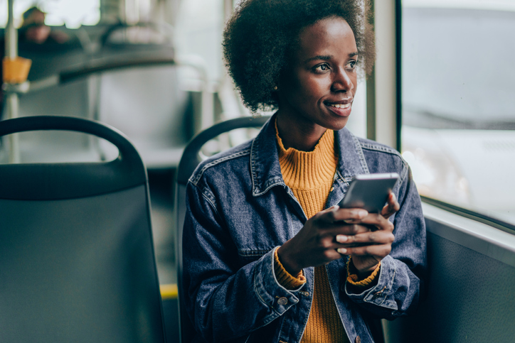 Young woman traveling by bus and using smart phone.