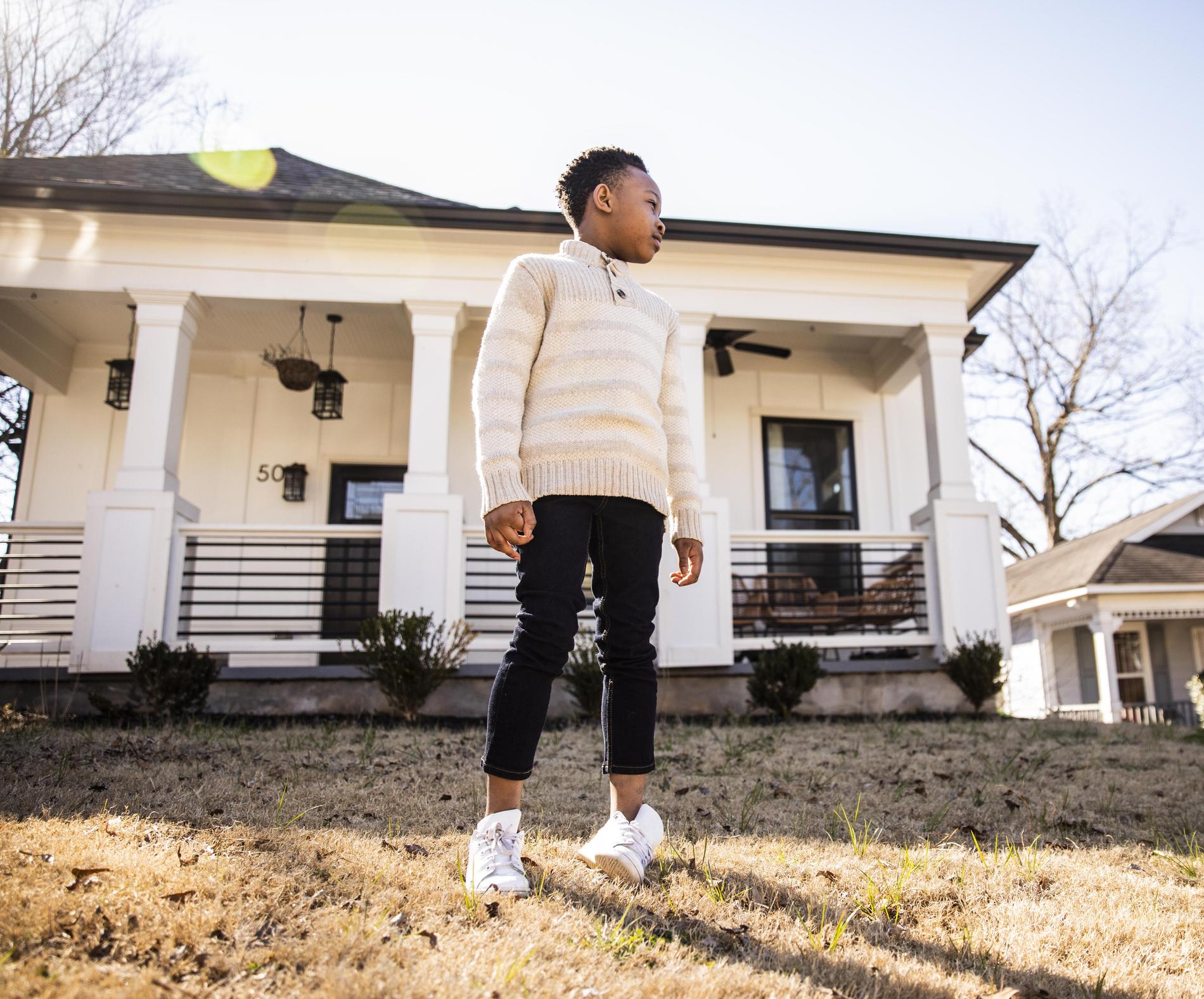 Portrait of young boy in front of home