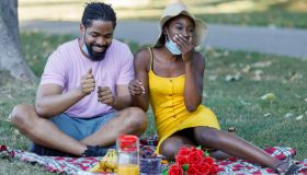 Happy Young African Couple is Having a Picnic Outside in Nature During a Virus Time.